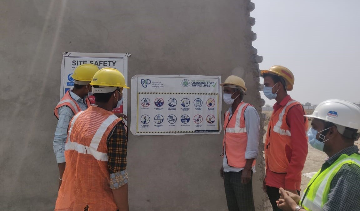 Workers on the Kota Grain Mandi project discussing the PIDG Life-Saving Rules which have been put up on the project site.